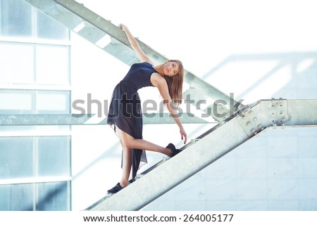 Young contemporary ballerina dancing on the staircase - stock photo