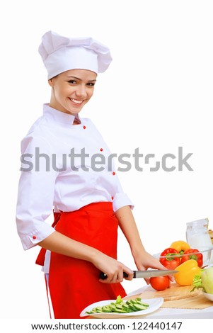 Young cook preparing food wearing red apron - stock photo