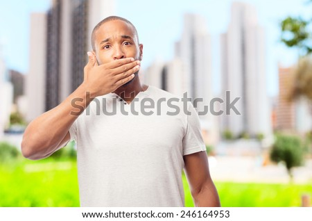 young cool black man covering his mouth - stock photo