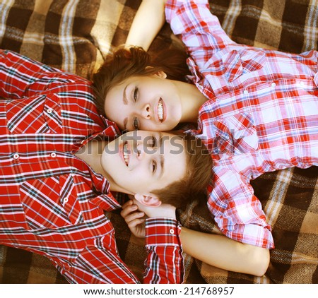 Young cool happy  together having fun in love, boyfriend and girl lying on the plaid looking up, top view - stock photo