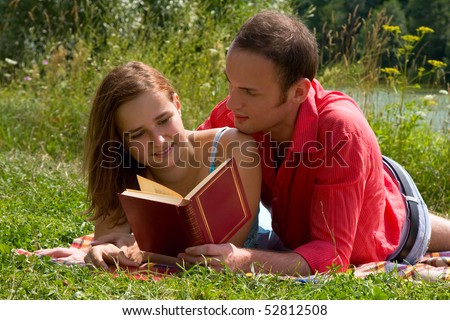 Young cople laying on a blanket on the grass on a hot summer day and reading book.  Woman and man are enjoying the sunshine in a park. Just happy couple relaxing. - stock photo