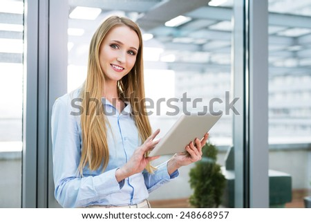 Young corporate worker standing and looking at the camera with a tablet in her hands - stock photo
