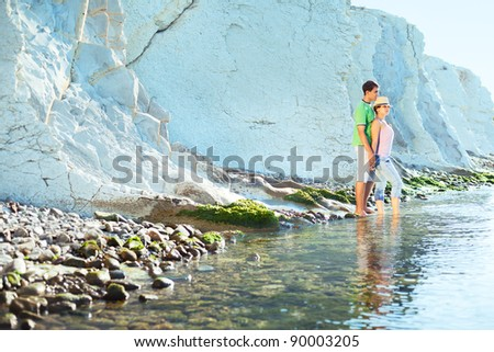 Young coupe walking on the rocky coast, sunny morning - stock photo