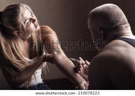 Young couple addicts. Man injects girlfriend drug into a vein - stock photo