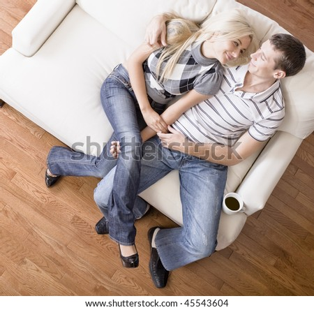 Young couple affectionately sit back on a cream colored love seat. Horizontal shot - stock photo