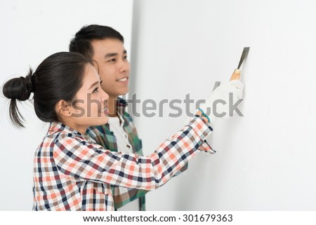 Young couple aligning a wall in their hew house - stock photo