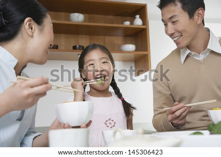 Young couple and daughter eating meal with chopsticks in kitchen - stock photo