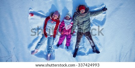 Young couple and little girl looking at camera while lying in snowdrift - stock photo