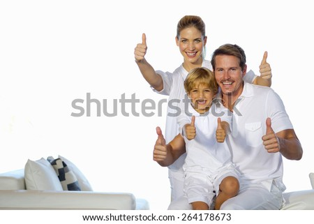 Young couple and their son sitting in white living room and gesturing thumbs up. - stock photo