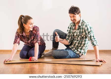 Young couple are installing laminate flooring in the room. - stock photo