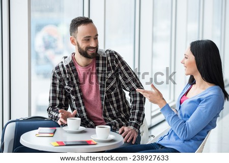 Young couple are  sitting with suitcase in international airport, are talking and drinking coffee. - stock photo