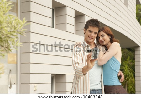 Young couple arriving at their new home and recording themselves at the house's entrance garden. - stock photo