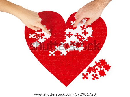 Young couple assembling a red puzzle heart shape on white background. - stock photo