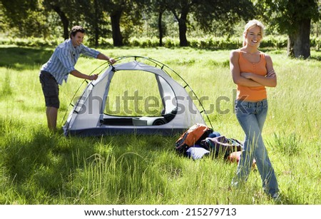 Young couple assembling tent on camping trip in woodland clearing, woman smiling, arms folded, portrait - stock photo