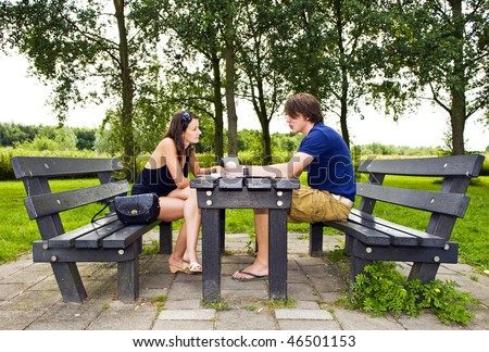 Young couple at a picnic table, talking and making travel plans - stock photo