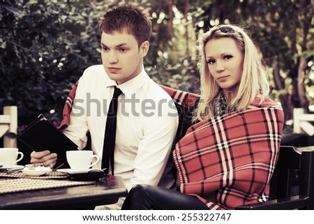 Young couple at a sidewalk cafe - stock photo