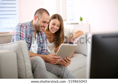 Young couple at home looking for tv progam - stock photo