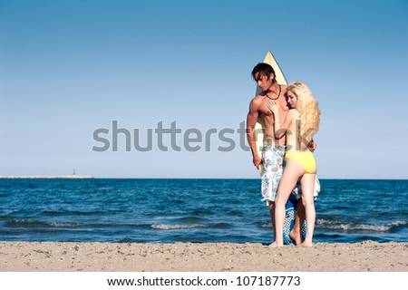 Young couple at the beach with surfboard with copy space. - stock photo