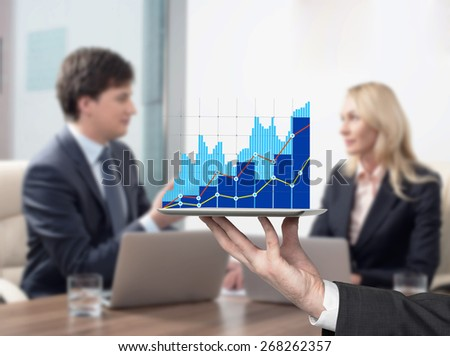 Young couple at the business meeting. Bar chart on the device. - stock photo