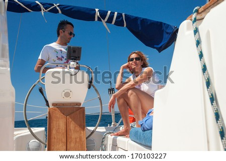 Young couple at the helm of a boat against a blue sky - stock photo