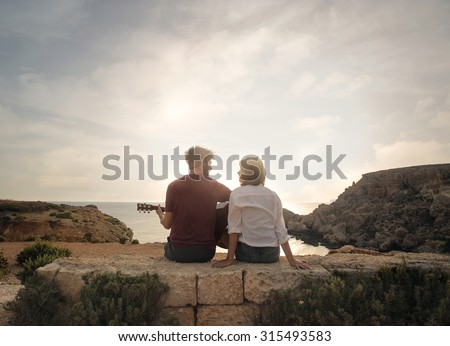 Young couple at the seaside playing guitar - stock photo