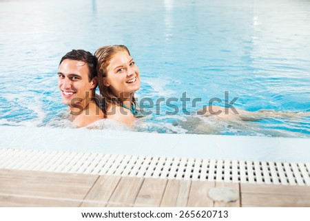Young couple at the swimming pool enjoying hydro massage - stock photo