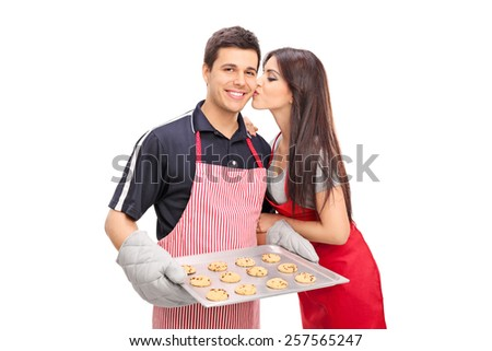 Young couple baking cookies together isolated on white background - stock photo