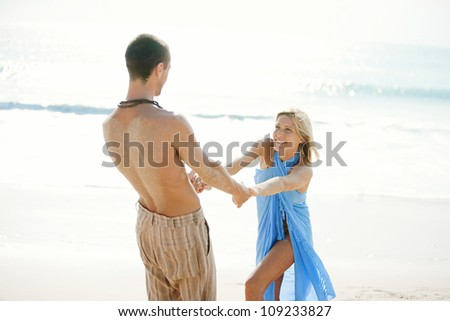Young couple being playful on a beach shore while on honeymoon. - stock photo