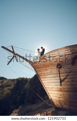 young couple bride and groom kiss on the bow of the ship restaurant. wedding theme. - stock photo