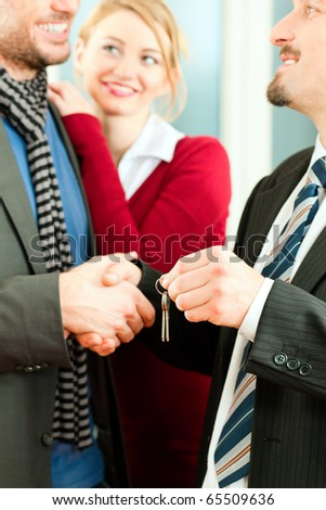 Young couple buying or renting a home or apartment, they are meeting the owner or real estate broker who has the keys; FOCUS on keys - stock photo