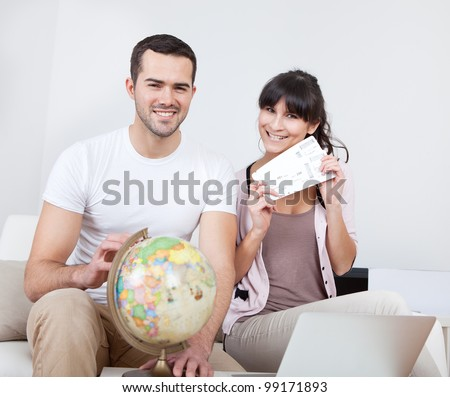 Young couple buying travel tickets online using laptop at home - stock photo