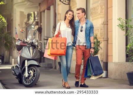 Young couple carrying shopping bags on city street - stock photo