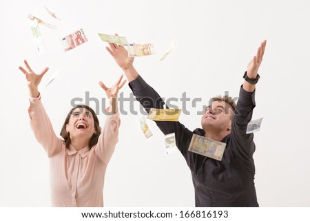 Young couple catching falling money - stock photo