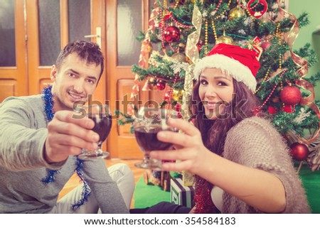 Young couple celebrating Christmas at home raising glasses of wine smiling , Two happy people beside Xmas tree and other New Year decoration - stock photo