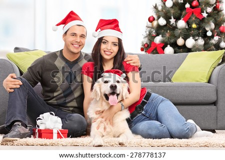 Young couple celebrating Christmas with their dog seated on the floor next to a modern sofa at their home - stock photo