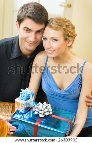 Young couple celebrating with champagne and gifts at home - stock photo