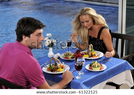Young couple celebrating with red wine at restaurant - a series of RESTAURANT images. - stock photo
