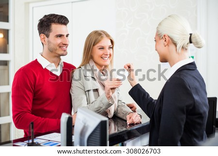 Young couple check in at hotel reception - stock photo
