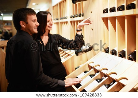 Young couple chooses the wine - stock photo