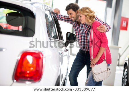 Young  couple chooses to buy a car in car dealership saloon - stock photo