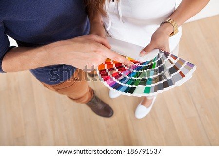 Young couple choosing color for wall from swatches at new home - stock photo