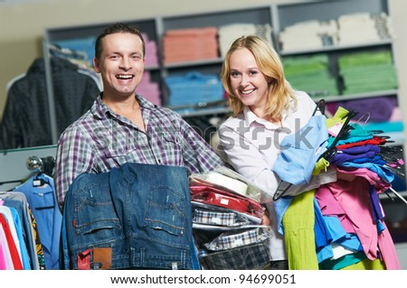 Young couple choosing shirt and necktie during clothing shopping at store - stock photo