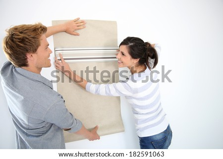 Young couple choosing wallpaper for new home - stock photo