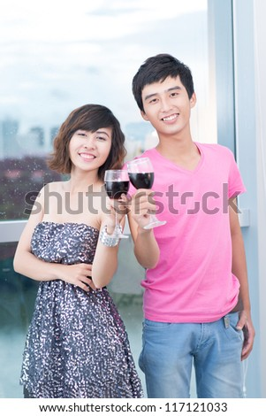 Young couple clinking glasses and smiling at camera - stock photo