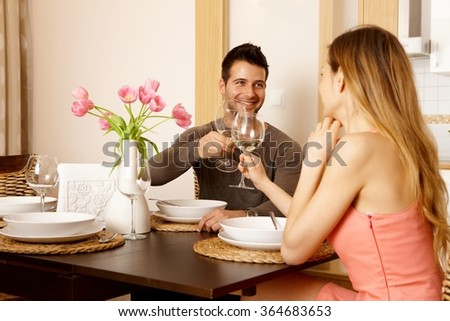 Young couple clinking glasses at home while having dinner, smiling. - stock photo