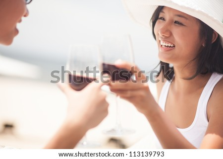 Young couple clinking wineglasses, the focus is on the girl - stock photo