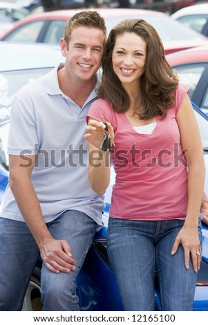 Young couple collecting new car from lot - stock photo