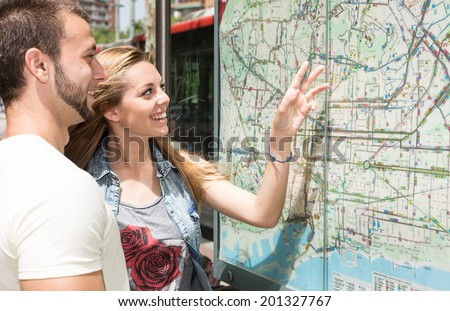 Young couple consulting a map in the city of Barcelona - stock photo