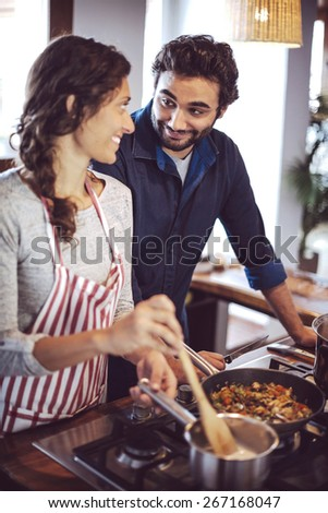 Young couple cooking. Man and woman in their kitchen - stock photo