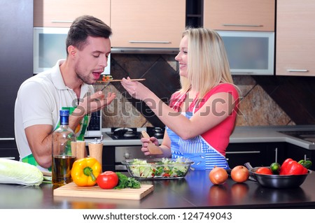 Young couple cooking - man and woman in their kitchen at home preparing vegetables for salad - stock photo